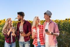 La gente que usa los girasoles al aire libre de charla del campo de los amigos del grupo del teléfono elegante coloca Fotos de archivo libres de regalías