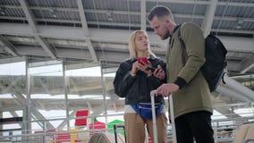 La gente que viaja se está colocando con equipaje dentro del pasillo del aeropuerto, usando smartphone almacen de video