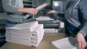La gente quita pilas de papel de un transportador tipográfico metrajes