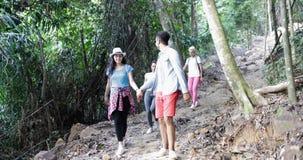La gente raggruppa con trekking degli zainhi su Forest Path Walk Downhill, sui giovani e sulla donna sull'aumento video d archivio