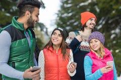 La gente raggruppa facendo uso dello Smart Phone che chiacchiera l'inverno all'aperto di camminata di Forest Happy Smiling Young  Fotografie Stock Libere da Diritti