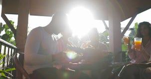 La gente raggruppa il cibo della prima colazione sul terrazzo, amici che comunicano mentre ha pasto all'aperto nella mattina video d archivio