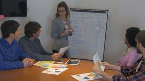 La gente raggruppa la discussione del progetto nuovo con i colleghi del gruppo archivi video