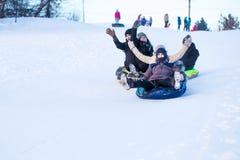 La gente resbala abajo de la colina de la nieve Imágenes de archivo libres de regalías