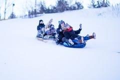 La gente resbala abajo de la colina de la nieve Fotos de archivo