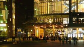 La gente riunisce il corridoio anteriore del cinema, riunioni di spettacolo di notte stock footage