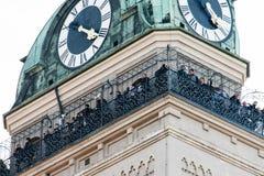 La gente riunita in cima a costruzione con l'orologio Immagine Stock Libera da Diritti