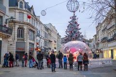 La gente riunita vicino ad una grande palla di vetro in una via ha illuminato la decorazione di Natale Immagine Stock Libera da Diritti