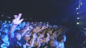 La gente sacude las manos en concierto de rock vivo en club nocturno Banda que se realiza en etapa proyectores metrajes