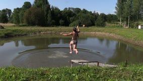 La gente salta dal ponte di legno in acqua del lago dello stagno il giorno di estate Fotografia Stock