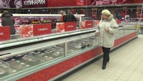 La gente sceglie i prodotti alimentari nel dipartimento della carne del supermercato stock footage