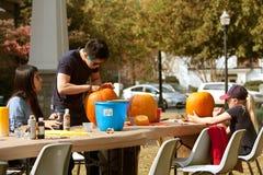 La gente scolpisce e dipinge le zucche di Halloween Immagini Stock Libere da Diritti
