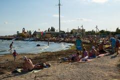 La gente sconosciuta gode di sulla spiaggia del mare di Azov Immagine Stock