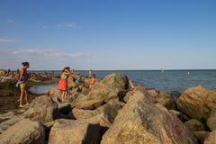 La gente sconosciuta gode di sulla spiaggia del mare di Azov Immagini Stock