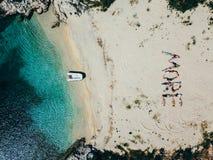 La gente scrive le loro parole sulla sabbia con i loro corpi fotografie stock