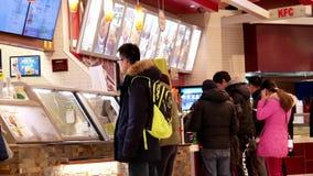 La gente se alinea para comprar el pollo de KFC en el área de la zona de restaurantes almacen de video