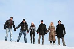 La gente se coloca en nieve y aferrarse a las manos fotografía de archivo libre de regalías