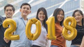 La gente se coloca en la sensación feliz con el globo 2018 del número Imagen de archivo