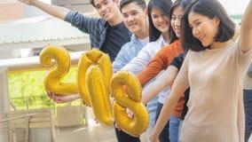 La gente se coloca en la sensación feliz con el globo 2018 del número Fotos de archivo libres de regalías
