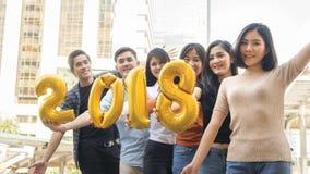 La gente se coloca en la sensación feliz con el globo 2018 del número Imágenes de archivo libres de regalías