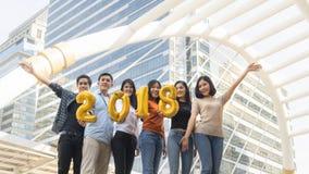 La gente se coloca en la sensación feliz con el globo 2018 del número Imagenes de archivo