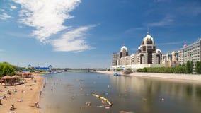 La gente se está bañando en un río a lo largo de un hyperlapse del timelapse de la playa y de un horizonte artificiales de Astaná almacen de video