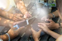 La gente se está sentando en el teléfono y el café de consumición en una tabla de madera en un restaurante fotos de archivo