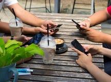 La gente se está sentando en el teléfono y el café de consumición en una tabla de madera en un restaurante fotografía de archivo