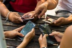La gente se está sentando en el teléfono y el café de consumición en una tabla de madera en un restaurante Foto de archivo libre de regalías