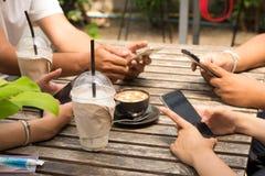 La gente se está sentando en el teléfono y el café de consumición en una tabla de madera en un restaurante imagenes de archivo