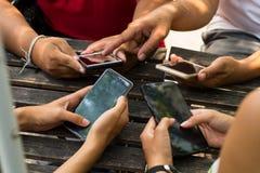 La gente se está sentando en el teléfono y el café de consumición en una tabla de madera en un restaurante fotos de archivo libres de regalías