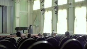 La gente se está sentando en la sala de conciertos, esperando comenzar del funcionamiento metrajes