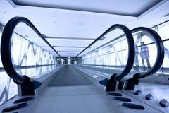 La gente se mueve en pasillo gris con las escaleras móviles Imagen de archivo libre de regalías