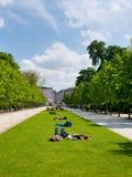 La gente se relaja en el césped en el parque Fotos de archivo libres de regalías