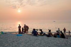 La gente se relaja en la playa en la puesta del sol Imagen de archivo libre de regalías