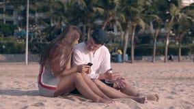 La gente se sienta en la arena amarilla y los textos morenos de pelo largo almacen de metraje de vídeo