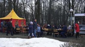 La gente se sienta en las tablas en el parque de la ciudad y come durante el día de fiesta Maslenitsa en BOBRUISK, BIELORRUSIA 03 almacen de metraje de vídeo