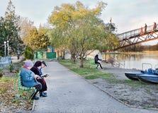 La gente se sienta en un banco de parque y los periódicos y los libros de la lectura. Imagenes de archivo