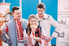 La gente se vistió en la ropa popular nacional que presentaba con una placa de crepes en manos Imagenes de archivo