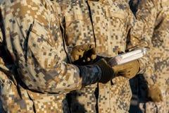 La gente se vistió en los uniformes del ` de los soldados, sosteniendo un libro Imagen de archivo libre de regalías