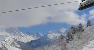 la gente in seggiovia alla stazione sciistica il giorno di inverno soleggiato contro il paesaggio nevoso della montagna stock footage