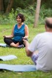 La gente senior durante l'yoga classifica in un parco Immagini Stock Libere da Diritti