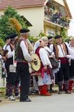 La gente si è vestita in vecchi vestiti di ethno a riso manuale che raccoglie la manifestazione il giorno soleggiato Fotografia Stock Libera da Diritti