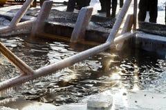 La gente si avvicina al ghiaccio-foro in lago congelato Fotografia Stock