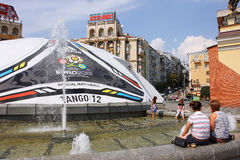 La gente si distende dalla fontana vicino alla sfera 2012 dell'EURO Immagine Stock