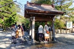 La gente si lava le mani prima della venuta al tempio a Kamakura, Giappone Fotografia Stock