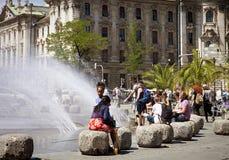 La gente si rilassa vicino alla fontana a Karlsplatz, Monaco di Baviera Immagini Stock