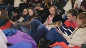 La gente si siede sul cuscino sul pavimento e sulla manifestazione in piedi di sorveglianza video d archivio