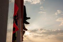 La gente si siede sul traghetto, le sue gambe ciondolante sopra il mare Immagini Stock