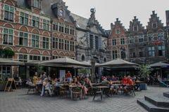 La gente si siede in un caffè nella parte centrale della città fra le costruzioni medievali fotografia stock libera da diritti